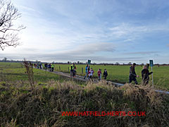 Tail of the march coming across the fields at the end of the footpath